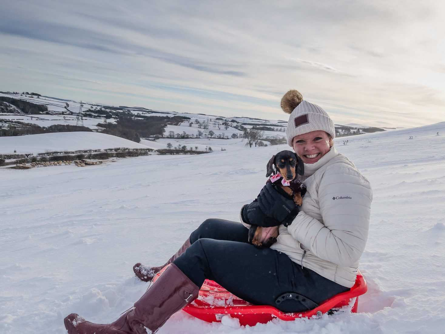Carmen sledding with our office mascot!